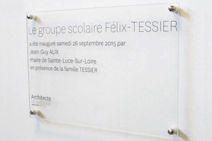 Plaque commémorative en Plexiglas® fixée sur un mur avec des entretoises